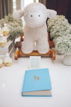 Stuffed animals, baby's breath, and children's books as baby shower decor