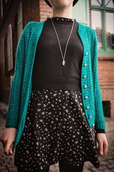 teal cardigan over black floral mini dress and black tights with boots