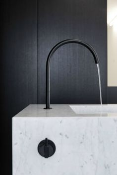 Beautiful white marble wash basin with graceful black water tap by Stein van Rossem.