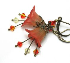 These lovely and feminine handmade art nouveau vintage style earrings feature two-toned orange sunrise frosted Lucite flowers which blend gracefully from yellow to orange. 4mm faceted Swarovski crystal bicones in gorgeous citrine and two-toned fire opal dangle from antiqued brass stamens. The flowers are wrapped in antiqued brass leaf bead caps and 6mm fire opal Swarovski crystal bicones sit atop in antiqued brass bead cups. Earrings dangle approximately two inches (50.8mm) from lead and…