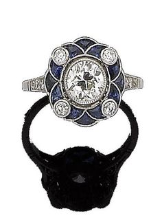 A sapphire and diamond cluster ring Designed as a flowerhead, the stamen set with a brilliant-cut diamond in collet-setting, within a calibré-cut sapphire petal surround highlighted with four collet-set old brilliant-cut diamonds, between brilliant-cut diamond shoulders, to a pierced gallery