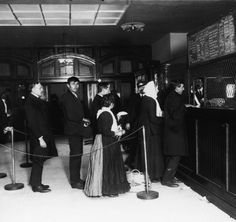 Customers wait in line at a teller's window in a bank on Ellis Island on Feb. 18, 1910. A board posted to the right of the window includes conversion prices (quoted by American Express) for gold, silver, and paper into a number of different currencies.