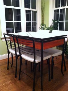 Refurbished 1950's enamel top table and metal chairs with white vinyl upholstery.