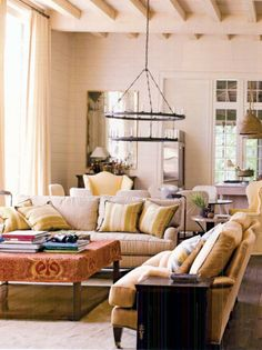 sofas, coffee table (minus the fabric slipcover), chandelier, dining area, open to kitchen (designed by Bill Ingram, via Southern Accents Jul/Aug 2009)