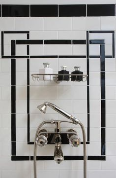 Art deco shower features black and white tiles lined with a metal shower caddy and a glam shower kit.