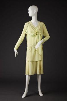 Dress 1920-1929. Chartruese Long Sleeved Silk Tunic Shift With Lime Green Fagotting On The Collar and Edge Of Sleeves. Separate Skirt Has Full Slip Top. V Neck With Side Collar That Ends In Inserted Scarf. Collar Has Embroidered Tennis Racket Detail and This Embroidery Is Also On Small Tunic Pocket. Low Hip Detail With Separate Self Fabric Belt. Full Slip Has Dropped Hip Skirt With Stitched Down Pleats In Front The Goldstein Museum of Design