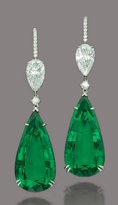 A PAIR OF MAGNIFICENT EMERALD AND DIAMOND EARRINGS The two pear-shaped emeralds, weighing 23.66 and 23.55 carats, suspending from two brilliant-cut diamonds and two pear-shaped diamonds, weighing 2.14 and 2.01 carats, to the pavé-set diamond hook, mounted in platinum, 6.0 cm