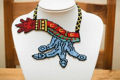 The symbol in the language of the Aztecs/Mexica (Náhuatl) was atl tlachinolli, meaning 'water, burnt (or scorched) earth'. The metaphor, Mexica, Loom Beading, Aztec, Crochet Necklace, Beads, Trending Outfits, Unique Jewelry, Tattoos, Handmade Gifts