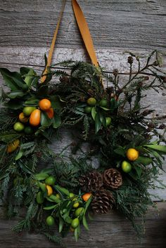 A beautiful wreath made from assorted greenery and adorned with orange berries and evergreen cones.| Flickr - Photo Sharing!