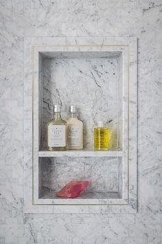 A walk in shower features walls lined with gray marble fitted with a tiled niche with shelf.