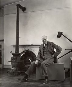 """EDWARD HOPPER, 1948  FROM THE HEILBRUNN TIMELINE OF ART HISTORY:  """"When Abbott arrived at Hopper's studio on Washington Square North, she was intending to use some of his paintings as a background. Instead, Hopper's wife suggested that she pose him in front of the bare, worn walls of the studio itself. In the resulting image, Hopper is an austere, angular figure. At the left stands a potbellied stove in front of a fireplace; at the right......."""" Photographed by BERENICE ABBOTT."""