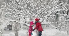 Crianças constroem boneco de neve em um parque em Bucareste, na Romênia.  Fotografia: Vadim Ghirda/AP.