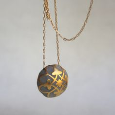 This Praline Ball Necklace rocks our world. A concrete pendant dangles on a gold fill chain, featuring an intricate painted gold-plated design by Hadaas Shaham