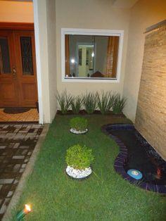 Na fachada da casa. Para o caminho de entrada, chão de tijolo à vista. Pedras brancas dão destaque ao espaço verde.