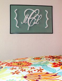Custom wooden monogram mounted on fabric framed in poster frame.  By Catie Henoch at Refined Design.