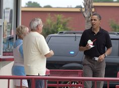 U.S. President Barack Obama (R) eats his mint chocolate chip ice cream as he talks to the Bruster's Real Ice Cream shop owners Joan and Larry Epperly August 15, 2010 in Panama City Beach, Florida.