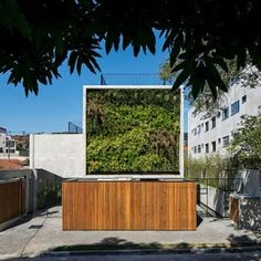 Wall of bushy plants fronts São Paulo  housing block by TACOA