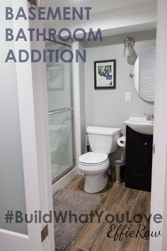 Faux Wood Tile Flooring, Glass Shower Doors, And A Frosted Glass Out Swing  Door In This Basement Bathroom Addition