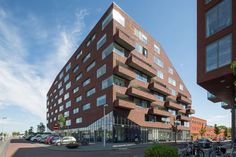 Contrast apartment building by KCAP, Leidsche Rijn, Netherlands - The balconies along the side streets are half integrated in the block to as set back from the noise. The building is composed as a robust block with large horizontal windows and brick balconies, resting on a glass plinth.