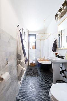"""Sandie says that """"sticking with two or three colors throughout the space and adding depth with textures will open up a small bathroom. For example, here we added visual textures with the marble subway tiles, and we juxtaposed the black floor tiles with light grouting."""""""