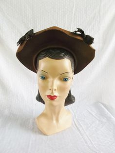 1940s clam shell style hat made of light brown felt with dark brown bow trim. Netting encircles the crown. Can be worn pushed back or tilted forward. Label: New York Creation.