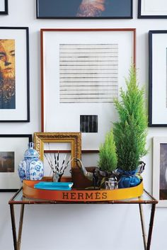 Brass faux bamboo wall shelf with Hermes tray, Ming porcelain urn, mini topiaries, gallery wall, etc.