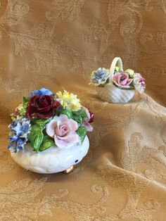 VINTAGE LOT OF STAFFORDSHIRE AND ROYAL DOULTON SCULPTURAL FLOWERS INCLUDING A FOOTED BOWL AND SMALL BASKET. SOME LOSS BUT OVERALL NICE DISPLAY CONDITION.