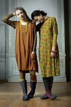"""Herbstmode 2012 - Kleider der Kollektion """"Mollig & Gemütlich"""":  Wunderschöne Kleider aus Modalgewebe und Trikot werden vor einer tollen Kulisse präsentiert. Auf der linken Seite ist ein curryfarbenes Kleid mit aufgesetzter Tasche zu sehen. Das rechte Model trägt das sharonfarbene Kleid 'Chestnut'. Es hat halblange Ärmel, wellige Picotnähte am Saum- und Armelabschluss und eine kleine Spitzenborte am Ausschnitt."""