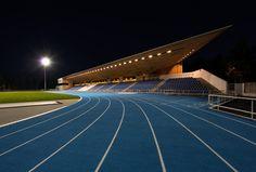 Wooden spike shelters grandstand at Estonian stadium by KAMP Arhitektid