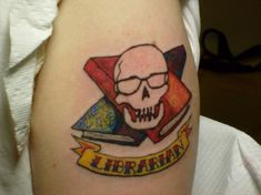 """Prefer your ink a little more hardcore than most of these librarian tattoos? Then, you'll probably approve of Jason Puckett's tattoo by Ron Hendon of Midnight Iguana Tattooing that features a bespectacled skull with """"crossbooks"""" and a """"librarian"""" banner. - Mental Floss"""