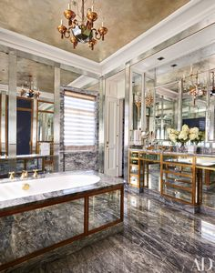 The master bath in this Minneapolis home decorated by Michael S. Smith shimmers with antiqued-mirror panels and a ceiling silver-leafed by artisan Maureen Lyttle; the chandelier is a circa-1930 design by Elsa Schiaparelli for Baguès, and the tub fittings are by P. E. Guerin.