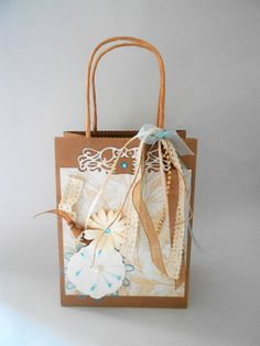 A hand decorated vintage style gift bag Made of quality brown paper with twisted paper handles that i have decorated with handmade die cut flowers in cream card with turquoise accents on cream vintage leaf paper with a filigree cutout design, a selection of ribbons, lace and beads in colours of cream, pale brown and pale turquoise on the front and tied round the handle with a bow and draped down the front...  A gift tag (not shown) hangs from the right with any name of your choice  Bag size…