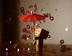 Amazon Box Guy holding a cocktail umbrella while confetti hearts rain down on him. Love's in the air!!!