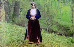 An Armenian woman in national costume poses for Prokudin-Gorskii on a hillside near Artvin (in present day Turkey), circa 1910.