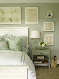 Beautiful sea green grasscloth wallpaper with framed map art work and small convex mirror. Beadboard style bed, white bedding with green and blue accent pillows. Chunky crystal lamp, sea green nightstand and sisal rug.