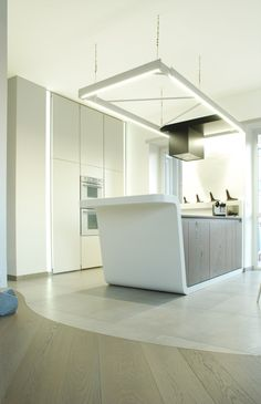 White corian kitchen | by a3lier, White corian, black stone, hash wood and hanging white Painted steel hood with light