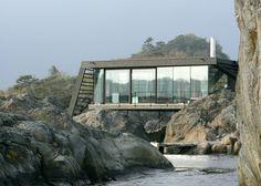 På en lille ø har man placeret en helt unik bygning kun få meter fra vandet, som nærmest smelter ind i den norske kysts barske og smukke natur.