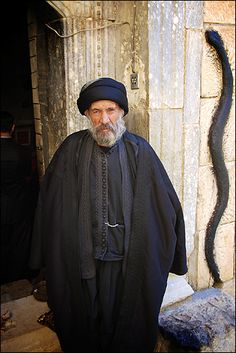 old man at Lalish - Yazidis venerate depictions of Serpents, this one carved into the doorway is covered in soot.