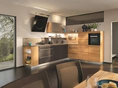 A harmonious mix of materials consisting of natural wood, stainless steel, and coloured glass in bronze and dark brown, make the kitchen into a real head-turner! Team 7, Colored Glass, Natural Wood, Kitchen Cabinets, Loft, Interior, Modern, Furniture, Fitted Kitchens
