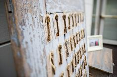 Hang keys on an old door as guests favor and escort cards.