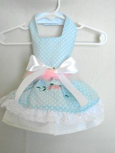 Lovely spring dress in a blue and white polka dot. Embroidery flowers on the skirt with a removable pink boa and white satin bow. All dresses are completely lined. 25.00