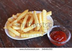 Fresh French fried before the big meal on the beautiful holiday and tasty tomato sauce on the wooden table.  - stock photo