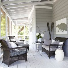 There's no better place to relax in the summertime than on a screen porch. This outdoor room features a soothing blue-gray color scheme as well as wicker furniture stuffed with plush pillows. A pair of oars and an oversize animal painting exude a weathered look thanks to their aged patinas.