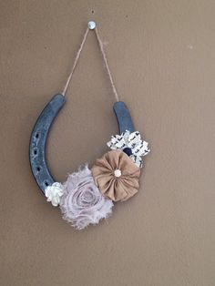 Horseshoe wall hanging. Easy to make and inexpensive. All you need is hot glue, twine, fabric flowers (I bought mine at Hobby Lobby) and horseshoes (can be bought from any farm store or anyone who shoes horses). Just glue the twine on the back side of the shoe in the groove and arrange your flowers how you'd like and there you go. Please note that I used a high temp glue.