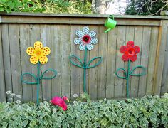 Dollar store flowers turned into garden art with hoses for leaves and stems