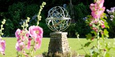 Stainless steel armillary sphere surrounded by flowers