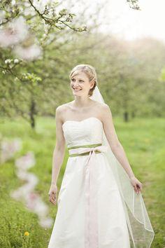 hochzeitskleid mit weitem, gerafften rock, breitem gürtel in rosa- grün mit dicker schleife vorne zum binden, breite rosa bänder zum herunterhängen, corsage mit blumen bestickt (Foto: Hanna Witte) (http://www.noni-mode.de)