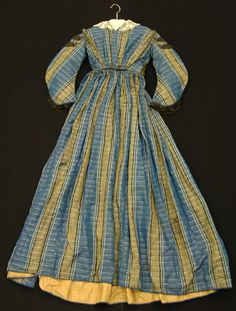 1863-1865 One-piece silk taffeta wedding dress with black lace trim. The original neckline has been altered to form a V-neck. Though there are no closures on the bodice, the lining has a hook-and-eye closure at its front. The skirt is evenly pleated at the waistline.