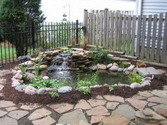 Garden and Patio, Easy And Simple Backyard Landscaping House Design With Ponds Surrounded By Small Garden With Stone And Mulch Plus Low Waterfall And Black Iron Fence Ideas ~ Simple Landscaping Ideas