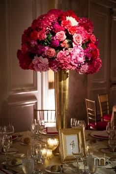 Red and pink large arrangements with greenery and a gold pedestal vase